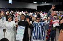 United Methodists who support the full inclusion of gay and lesbians in the life of church, including Lea Matthews, at left, stand in a silent demonstration May 18 inside the Oregon Convention Center in Portland, Ore., during the 2016 United Methodist General Conference. They entered the plenary hall and silently circled the center altar. Photo by Kathleen Barry, UMNS