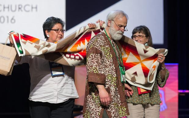 "The Rev. L. Fitzgerald ""Gere"" Reist II (center) is honored for his years of service as secretary of the United Methodist General Conference during the denominational meeting May 20 in Portland, Ore. Presenting him with a blanket are Cynthia Kent (left) and Raggatha Calentine. Photo by Mike DuBose, UMNS"