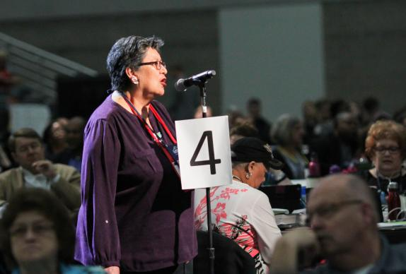 Cynthia Kent, chairperson of the Native American International Caucus, speaks on a petition that asks The United Methodist Church raise awareness of the harm caused by some sports teams by mascots and/or symbols promoting expressions of racism and disrespect of Native American people. She spoke during the May 19 plenary session of the 2016 General Conference in Portland, Ore. Photo by Maile Bradfield, UMNS.