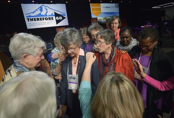 Women bishops pray over Bishop Hope Morgan Ward during a recess in the United Methodist General Conference in Portland, Ore. Ward presided over an emotional debate on proposed Rule 44, which would place deliberations over sensitive issues into small discussion groups. Photo by Paul Jeffrey, UMNS.