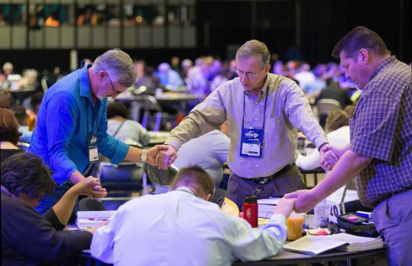 The Rev. Dan Bryant (center) leads fellow delegates from the East Ohio Conference in prayer May 17 following a speech by Bishop Bruce Ough in which he said the bishops are not supporting any plan for a split of The United Methodist Church during the denomination's 2016 General Conference in Portland, Ore. Photo by Mike DuBose, UMNS