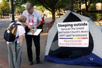 The Rev. Mike Tupper talks to a volunteer during his tent witness at the 2016 General Conference in Portland, Ore. Tupper recently agreed to a resolution of a same-sex marriage complaint. Photo by Kathleen Barry, UMNS
