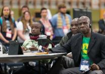 Delegate Pierre Kasongo (right) and other members of the Tanganyika delegation vote on legislation while supporters of full rights for LGBTQ persons in the life of The United Methodist Church stand with their mouths taped shut outside the bar of the 2016 United Methodist General Conference in Portland, Ore., to symbolize the way LGBTQ people feel they are silenced by the church. Photo by Mike DuBose, UMNS