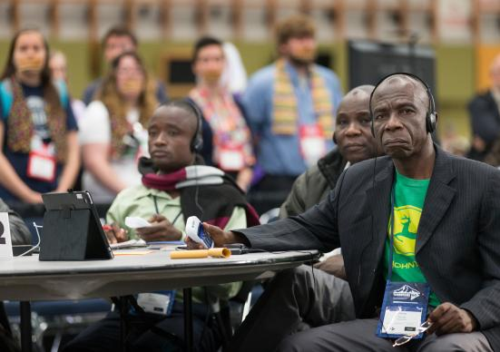 Delegate Pierre Kasongo (right) and other members of the Tanganyika delegation vote on legislation while supporters of full rights for LGBTQ persons in the life of The United Methodist Church stand with their mouths taped shut outside the bar of the 2016 United Methodist General Conference in Portland, Ore., to symbolize the way LGBTQ people feel they are silenced by the church. Photo by Mike DuBose, UMNS.