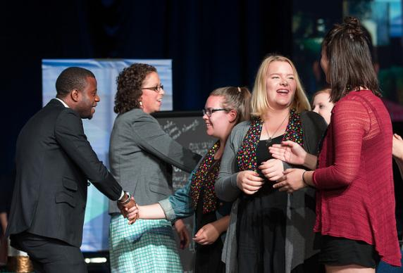Peter Cibuabua of the Central Congo Conference (left) and Chelsea Spyres of the Peninsula-Deleware Conference (second from left) celebrate with other presenters at the conclusion of the young people's address at the 2016 United Methodist General Conference in Portland, Ore. Photo by Mike DuBose, UMNS.