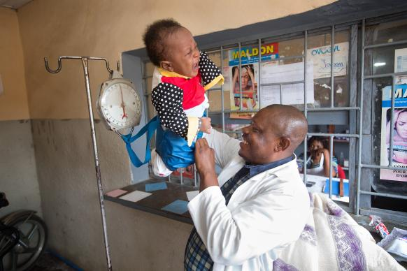 "Lofato Feliobola removes a baby from the seat used to weigh him at The United Methodist Church's Mangobo Health Center in Kisangani, Democratic Republic of Congo. A new ""Abundant Health"" campaign for the denomination would reach one million children with lifesaving interventions between 2017 and 2020. Photo by Mike DuBose, UMNS"