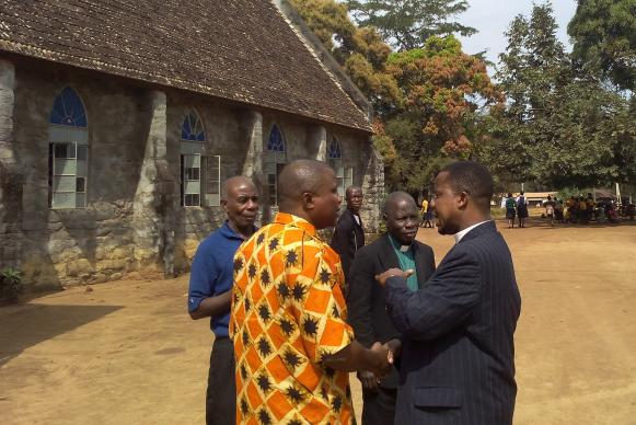 The Revs. David Tokpah (right) holds the hand of the Rev. Samuel Quire in conversation at the Gompa District Conference in Buchanan City, Nimba County, Liberia.