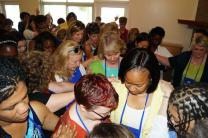 Women in the Southeastern Jurisdiction pray for Bishops-elect Sue Haupert-Johnson (in green-and-blue) and Sharma Lewis (in yellow-and-white) a day before their consecration. United Methodists already have elected a record number of women bishops this year. Photo by Jasmine Haynes, Mississippi Conference