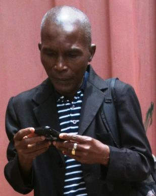 Julu Swen in Monrovia, Liberia, receives a text message on Ebola, written by Liberia Area Bishop John G. Innis. United Methodist Communications transmitted information.