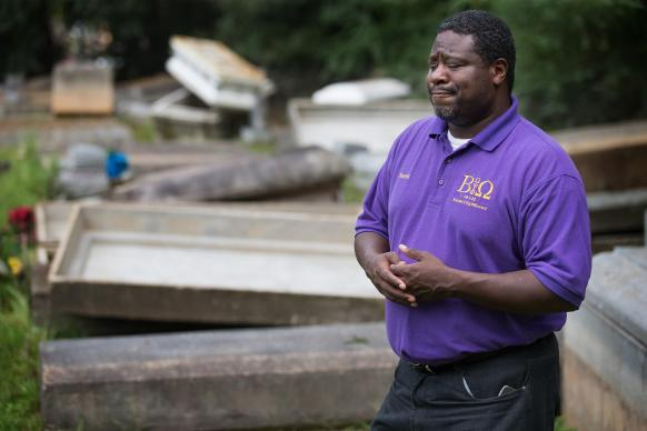 The Rev. Kermit Roberson surveys flood damage at Roberts United Methodist Church's Plainview Cemetery in Denham Springs, La., where floodwaters lifted many caskets out of their concrete burial vaults. Photo by Mike DuBose, UMNS