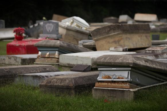 Caskets and concrete burial vaults lay in a jumble at Roberts United Methodist Church's Plainview Cemetery in Denham Springs, La., after rising floodwaters lifted them out of the ground. Church and state officials are working to identify and rebury the displaced remains. Photo by Mike DuBose, UMNS
