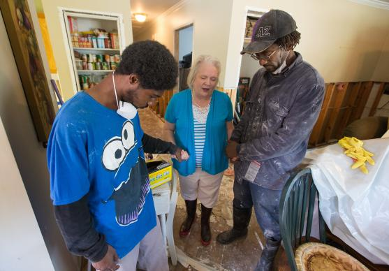 The Rev. Susan Ferguson (center) prays with Trent Noel (right) and his son, Jay Barnes, while the two men take a break from gutting flood-damaged drywall at the home of Noel's mother in Lafayette, La. Ferguson is pastor at Asbury United Methodist Church in Lafayette.