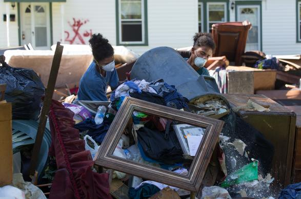 Jeremain (left) and Jeremaih Robinson pile up ruined furnishings from a home that was heavily damaged by flooding in Baton Rouge, La. The 16-year-old twins were part of a volunteer team from First United Methodist Church in Baton Rouge. Photo by Mike DuBose, UMNS.