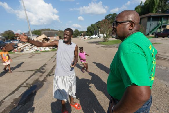 The Rev. Robert Johnson (right) visits with Ronald Redmond and his children while checking on the welfare of residents at a flood-damaged apartment complex in Duson, La. Johnson is pastor of Louisiana Avenue United Methodist Church in Lafayette.