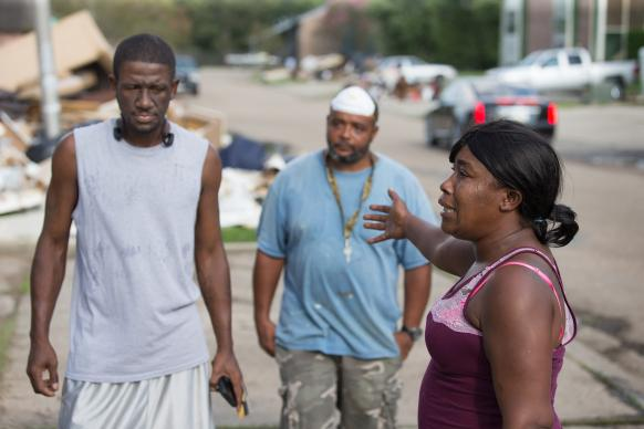 Tanya Wade (right) expresses her concern for other residents of a flood-damaged apartment complex in Duson, La. Joining her are Ronald Redmond (left) and Kevin Oliver.