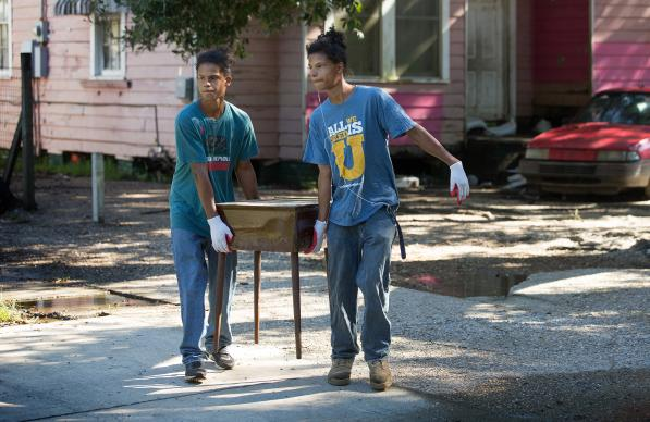Jeremaih (left) and Jeremain Robinson remove a waterlogged table from a home that was heavily damaged by flooding in Baton Rouge, La. The 16-year-old twins were part of a volunteer team from First United Methodist Church in Baton Rouge. Photo by Mike DuBose, UMNS