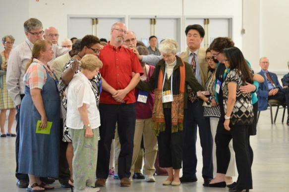 "Church members stand with the Rev. Donald ""Skip"" Smith, who said he would leave the New England Conference after the non-conformity vote. He later told his district superintendent that he would stay. Photo by Beth DiCocco, New England Conference"