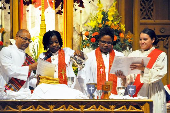 The two newly consecrated Northeastern Jurisdiction bishops serve Holy Communion during the worship service on July 15, assisted by two deacons. Bishop Cynthia Moore-Koikoi is shown, center left, while Bishop LaTrelle Miller Easterling is shown, center right. Photo by Melissa Lauber, Baltimore-Washington Conference