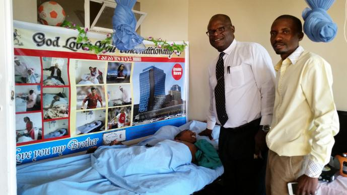 "The Rev. Lancelot Mukundu and Learnmore Kateguru visit by the hospital bed of Farai ""Joy"" Kanyemba at the United Methodist Nyadire Mission Hospital in Zimbabwe. Photo by Eveline Chikwanah, UMNS"