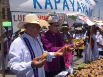 United Methodist Bishops Solito K. Toquero (left) and Rodolfo A. Juan break sweet potatoes for Holy Communion at a rally during the first State of the Nation Address July 25 by President Rodrigo R. Duterte of the Philippines in Quezon City. Photo courtesy of Darlene Marquez-Caramanzana