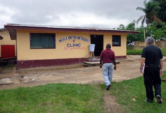 Two men walk toward the Weala United Methodist Church Liberia Clinic.