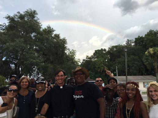 "At the end of an ecumenical ""Prayer Walk for Racial Peace,"" organizers and some marchers are shown under one of the rainbows that came out at the end of the march. Photo courtesy of Michael Beck"