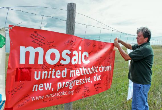 The Rev. David Wilson, superintendent of the Oklahoma Indian Missionary Conference, attaches banners from United Methodist churches supporting the Standing Rock Sioux' protest of the Dakota Access Pipeline. Wilson was at the protest camp, near Cannon Ball, N.D., on Sept. 10. Other United Methodist pastors will be gathering there for an interfaith clergy event on Nov. 3.