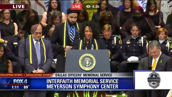 The Rev. Sheron Patterson prays at a July 12 interfaith service in Dallas, honoring five police officers slain by a sniper. Video image from Fox4 News broadcast / North Texas Conference.