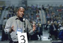 The Rev. Forbes Matonga, a clergy delegate from the West Zimbabwe annual conference, speaks to the United Methodist General Conference in Portland, Ore., on May 11. Matonga spoke in opposition to proposed Rule 44, which would allow small discussion groups to be used to handle sensitive themes. Photo by Paul Jeffrey, UMNS