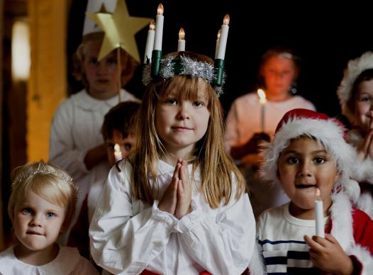 Around Christmas time in Sweden, one of the biggest celebrations is St. Lucia's Day celebrated by a girl dressing in a white dress with a red sash round her waist and a crown of candles on her head.