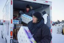 Members of the Oklahoma Indian Missionary Conference, including the Rev. David Wilson (left, in truck) and Justin Phillips, deliver supplies to water protectors at the Standing Rock Sioux base camp near Cannon Ball, N.D. Photo by Allen Buck