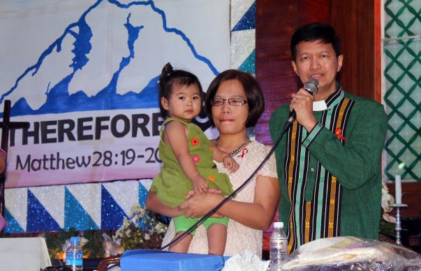 Bishop Pedro M. Torio Jr. speaks to the Philippines Central Conference after he was re-elected as a United Methodist bishop on Dec. 1. His wife, Joyce, holds their baby. Photo by Gladys Mangiduyos, UMNS