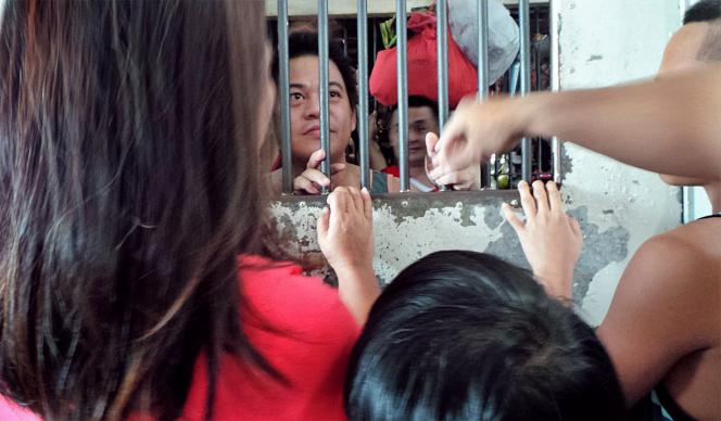 Inmates can see visitors through the bars of the custodial facility main gate of the Camalig Meycauayan City Jail in Bulacan, Philippines. The city jail is designed for 90 detainees, but has more than 200. Members of New Hill Burning Bush United Methodist Church recently distributed medicines to the inmates.