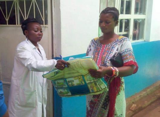 Anny Butunga Mwindulwa distributes a mosquito net to new mother Aziza Rachel outside the Irambo Clinic maternity ward in Bukavu, Democratic Republic of Congo. Photo by Philippe Kituka Lononga, UMNS.