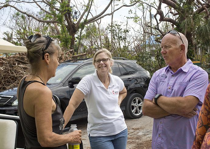 (From left) Denise Santos, the Rev. Laura Ice and Bob Cholka talk outside a Goodland distribution center located on the tip of Marco Island, Fla. Wesley United Methodist Church in Marco Island has reached out to the residents of the Goodland community. Santos is a volunteer from Goodland, Ice is recovery coordinator for the Florida Conference and Cholka is chairperson of the Wesley United Methodist Church council. Photo by Kathleen Barry, UMNS.
