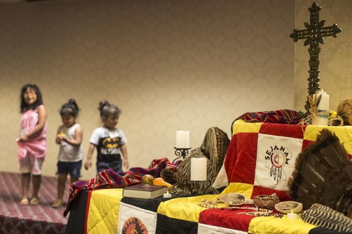 A display at the conference features symbolism of faith and Native American culture. Behind the table, descendants of the Lumbee tribe represent the future. Photo by Kathleen Barry, UMNS.