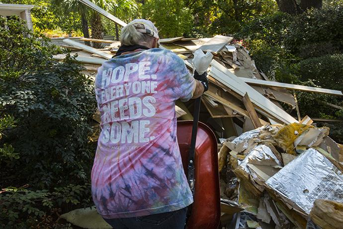 Helen Crowe from Chapelwood United Methodist Church in Houston dumps a load of debris in the front yard of a home flooded by Hurricane Harvey. Photo by Kathleen Barry, UMNS.