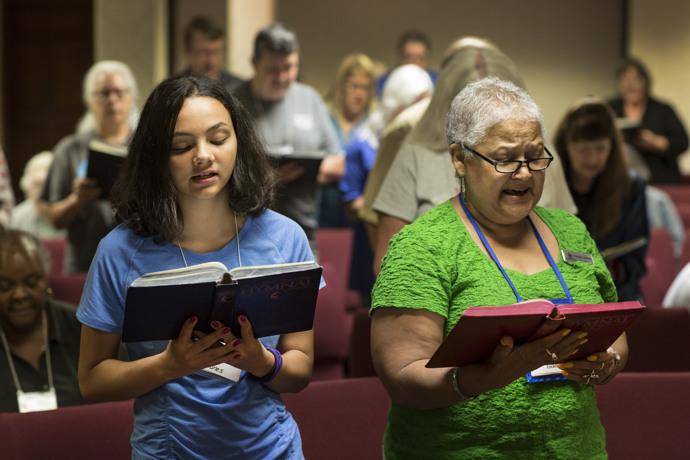 Sade Jones (left) and Connie Locklear sing during the opening worship. Photo by Kathleen Barry, UMNS.