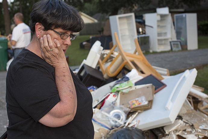 Sandy McCall looks through her furniture and flooded possessions on the street outside her home in Orange, Texas, after Hurricane Harvey. Photo by Kathleen Barry, UMNS.