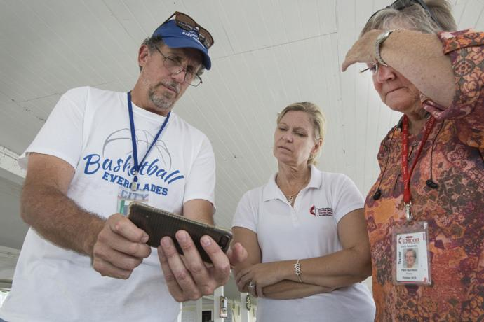 (From left) Jim Ragusa, principal of Everglades City School, shows photos of Hurricane Irma damage to the Rev. Laura Ice and Pam Garrison. Ragusa chose to ride out the storm with other residents.  Ice is recovery coordinator for the Florida Conference and Garrison is disaster response coordinator for the Florida Conference. Photo by Kathleen Barry, UMNS.