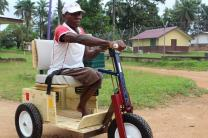 Abel Gbeadquoi sits on his Personal Energy Transportation vehicle, a gift from the United Methodist Women in Liberia. Photo by Julu Swen, UMNS.