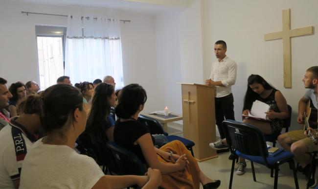 Gjergji Lushka preaches during the first worship service of the first United Methodist church in Durrës. The service was held in a three-room apartment that had been rented by the church to house services, fellowship and children's ministry. Photo by Jean Nausner