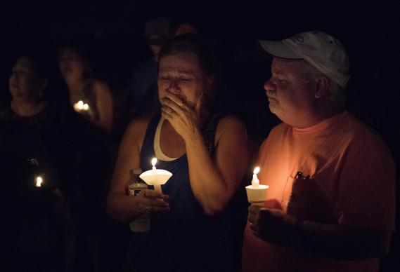 Mourners participate in a candlelight vigil for the victims of a fatal shooting at the First Baptist Church of Sutherland Springs, Sunday, Nov. 5, 2017, in Sutherland Springs, Texas. A man dressed in black tactical-style gear and armed with an assault rifle opened fire inside the church in the small South Texas community on Sunday, killing and wounding many. The dead ranged in age from 5 to 72 years old. AP Photo by Darren Abate.