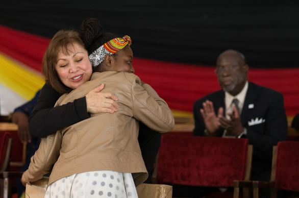 Bishop Minerva Carcaño (left) hugs Chiedza Chiwanza at the conclusion of Sunday worship during the 25th anniversary celebration for Africa University in Mutare, Zimbabwe. Chiwanza, a first-year humanities student, had just presented Carcaño a gift. At right is Bishop James Swanson. Photo by Mike DuBose, UMNS.
