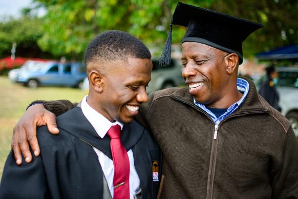 Keith Maraini Mudakureva (left) is congratulated by his father during Africa University's 2017 commencement. Mudakureva graduated with a Bachelor of Science degree in marketing. Photo courtesy of Africa University.