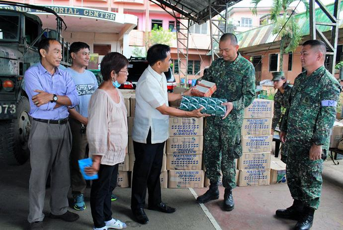 Bishop Rodolfo A. Juan (third from right), along with other clergy and lay people, distributes water and medicine to Marines. Photo courtesy of the Rev. Capt. Eduardo Copliting.