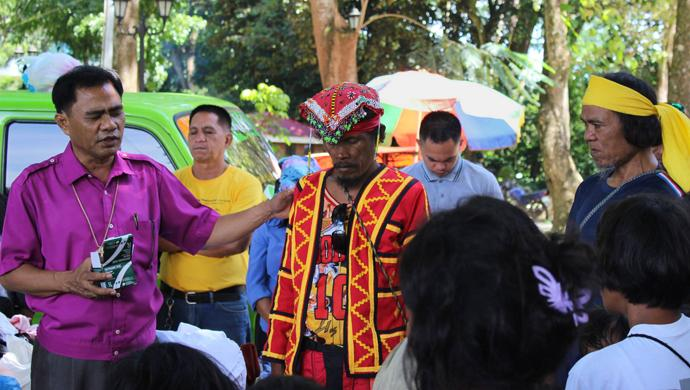 Bishop Rodolfo A. Juan (left) prays for a leader (red vest) at a camp for displcced people in Malaybalay, Philippines. United Methodists pooled their resources to provide relief to wounded soldiers and people displaced due to violence between the military and the Islamic State group or ISIS. Photo courtesy of Dan Ela.