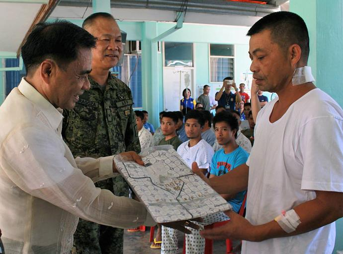 Bishop Rodolfo A. Juan (left), gives a set of pajama to an injured soldier during a two-day relief effort by Filipino United Methodists for wounded military and people displaced by violent conflicts in the Philippines. Photo courtesy of the Rev. Capt. Eduardo Copliting.