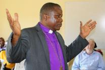 Bishop Samuel J. Quire Jr., raises his hands during regular devotion at the United Methodist Church in Liberia's central office on Oct. 27. The bishop is calling on all Liberians to shun violence as they prepare for a run-off presidential election.