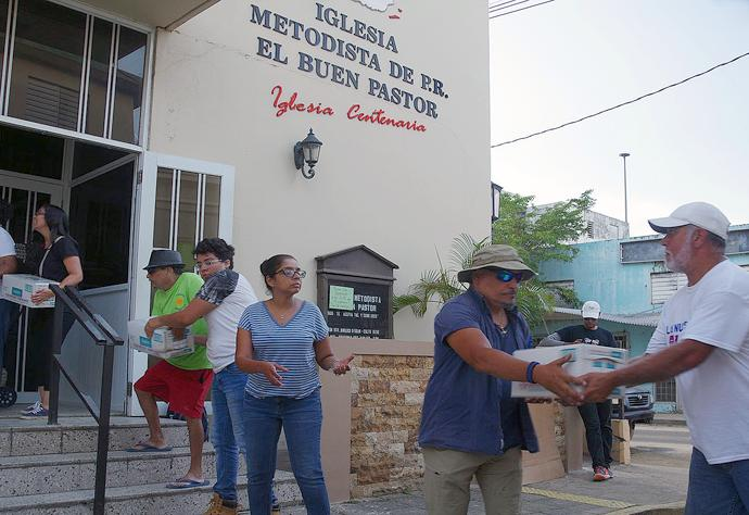A group of members and pastors from Methodist churches in the San Juan area form a human chain to unload supplies at the Utuado church in central Puerto Rico. The
